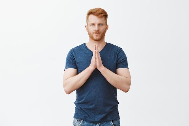 Portret van ernstig uitziende knappe volwassen roodharige met spieren, hand in hand in gebed, namaste gebaar maken of buigen in aziatische stijl, streng starend over grijze muur