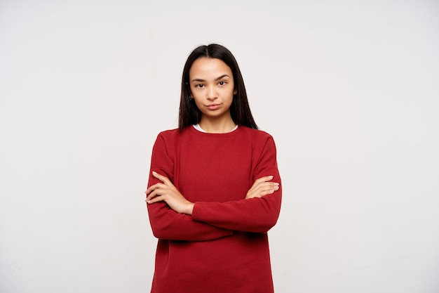Portret van ernstig, volwassen aziatisch meisje met donker lang haar. het dragen van rode trui en vouwen gekruiste armen op een borst. kijken naar de camera veroordelend, geïsoleerd op witte achtergrond