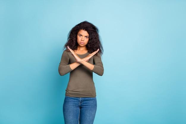 Portret van ernstig zelfverzekerd afro-amerikaans meisje kruis haar handen zeggen dat het verboden is afwijzen keuze besluit oplossing dragen casual stijl groene kleding denim jeans geïsoleerd over blauwe kleur muur
