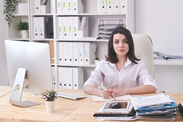 Portret van ernstige aantrekkelijke jonge onderneemster in witte blouse die aantekeningen maakt in dagboek in modern bureau