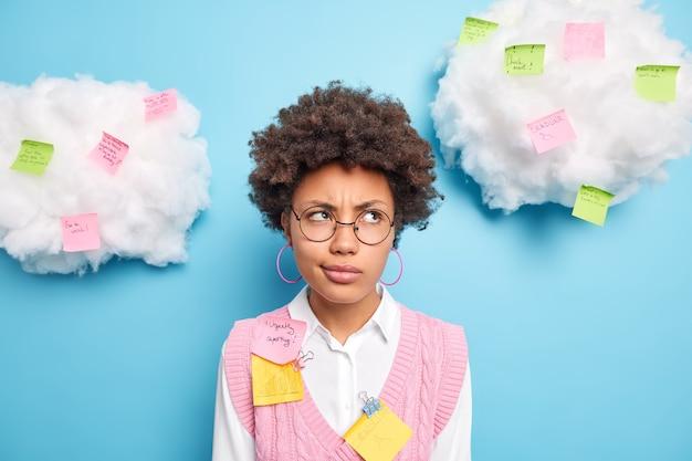 Portret van ernstige afro-amerikaanse student geconcentreerd weg met ontevreden doordachte uitdrukking schrijft herinnerende ideeën over kleurrijke plaknotities vormt tegen blauwe muur