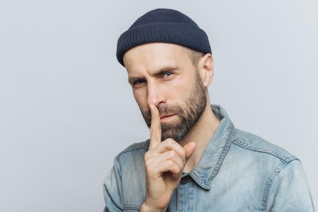 Portret van ernstige bebaarde man met aantrekkelijke look, houdt vinger op lippen, kijkt met geheime uitdrukking