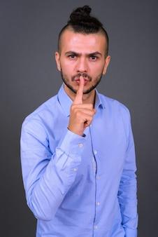Portret van ernstige bebaarde turkse zakenman met vinger op lippen