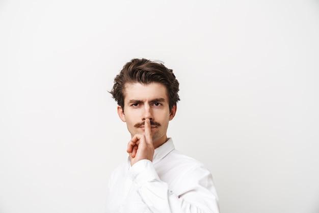 Portret van ernstige besnorde man met shirt met vinger op zijn lippen geïsoleerd op wit