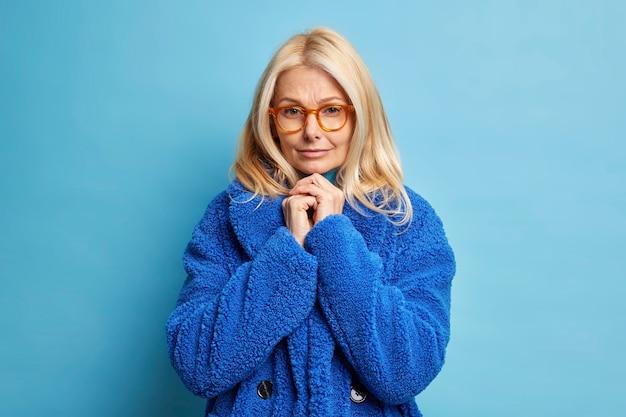 Portret van ernstige blonde vrouw houdt handen tegen elkaar gedrukt in de buurt van kin draagt optische bril en bontjas heeft mysterieuze look.