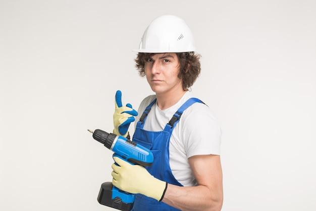 Portret van ernstige bouwersmens in witte helm met schroevedraaier die handschoenen en blauwe overall draagt.