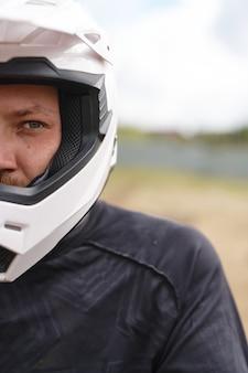 Portret van ernstige brutale motorrijder in helm en jas permanent buitenshuis