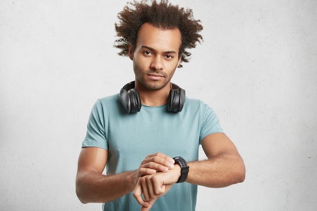 Portret van ernstige donkere man draagt blauwe t-shirt, luistert tracks met koptelefoon