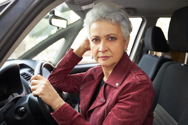 Portret van ernstige gepensioneerde vrouw met kort kapsel, zittend in de auto, rijexamen passeren, nerveus voelen.