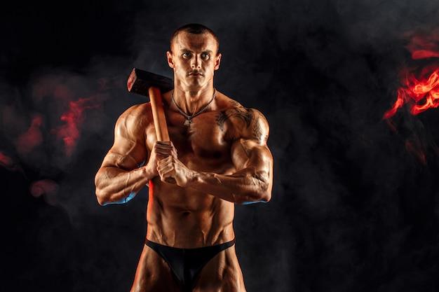 Portret van ernstige gespierde topless man met voorhamer