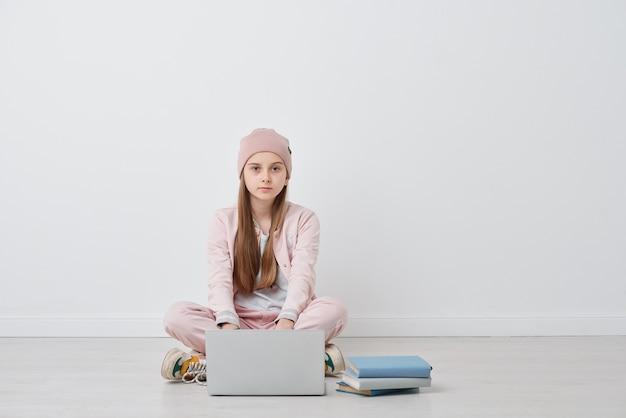 Portret van ernstige hipster tienermeisje in hoed zittend met gekruiste benen op de vloer en met behulp van laptop