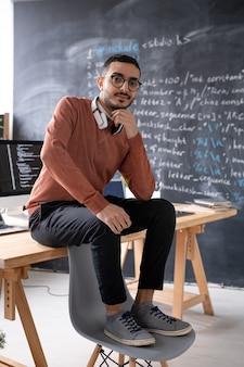 Portret van ernstige jonge arabische it-ingenieur zittend op tafel met voeten op stoel in modern kantoor met computerscript op bord