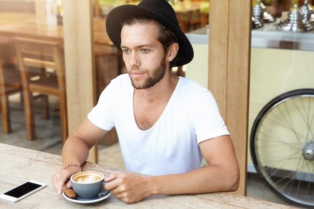 Portret van ernstige jonge bebaarde man in trendy hoed met cappuccino met koekje terwijl u alleen ontspant in café