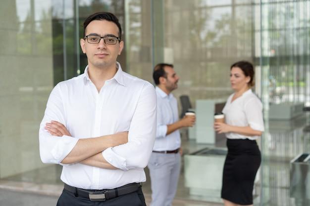 Portret van ernstige jonge kaukasische uitvoerende dragen brillen