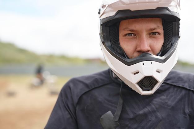 Portret van ernstige jonge mannelijke motorrijder in witte helm op off-road track
