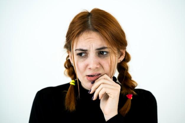 Portret van ernstige jonge vrouw die haar hand houdt om het denken onder ogen te zien geconcentreerd over iets