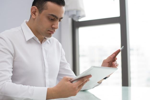 Portret van ernstige jonge zakenman die aan digitale tablet werkt