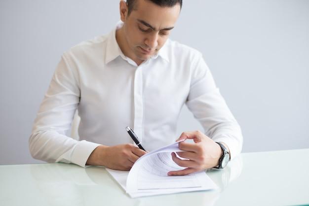 Portret van ernstige jonge zakenman die vragenlijst invullen