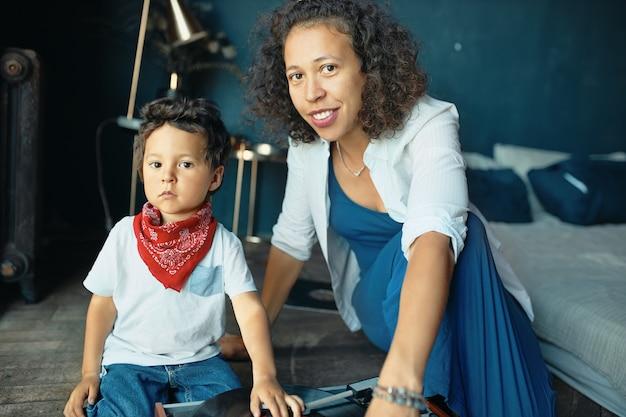Portret van ernstige kleine jongen met mollige wangen en rode hoofddoek om zijn nek zittend op de vloer met moeder