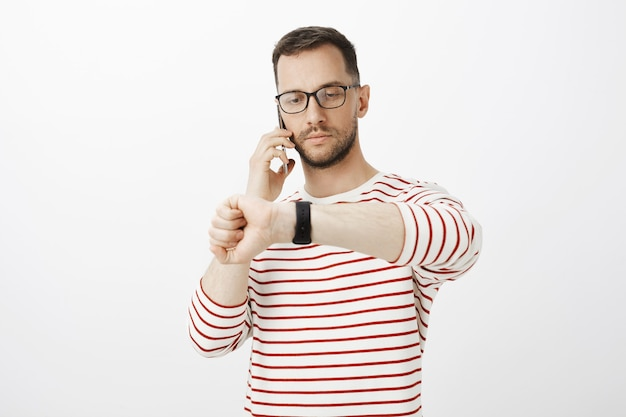 Portret van ernstige knappe zakenman in glazen, praten over smartphone en horloge kijken, omgaan met zakenpartner en tijd van vergadering beslissen