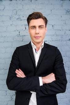 Portret van ernstige man in zwarte jas met gekruiste handen