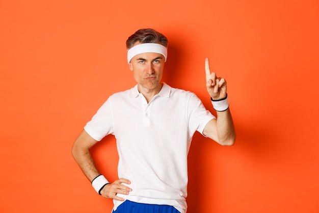Portret van ernstige mannelijke atleet van middelbare leeftijd, die sportkleding draagt