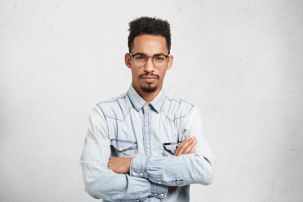 Portret van ernstige mannelijke baas heeft chagrijnige uitdrukking, geïrriteerd door werknemers,