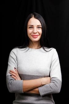 Portret van ernstige mooie vrouw met zwart haar, heeft minimale make-up, kijkt rustig naar de camera, draagt een witte trui, staat tegen zwarte ruimte, diep in gedachten.