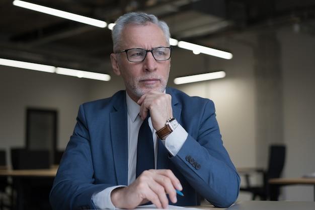 Portret van ernstige senior zakenman planning project, denken, wegkijken werken in kantoor