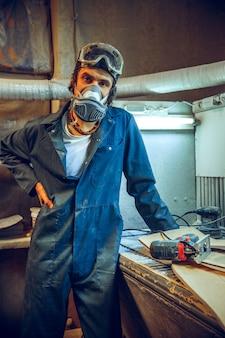 Portret van ernstige timmerman op zijn werkplek.