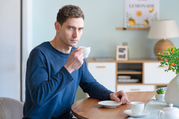 Portret van ernstige triest boos knappe jongen mooie jongeman is het drinken van thee of koffie uit wit
