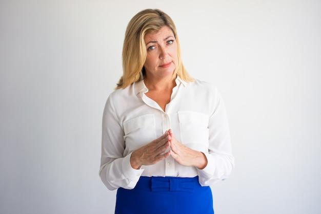 Portret van ernstige volwassen kaukasische vrouw in witte blouse die vingers samenbrengen.