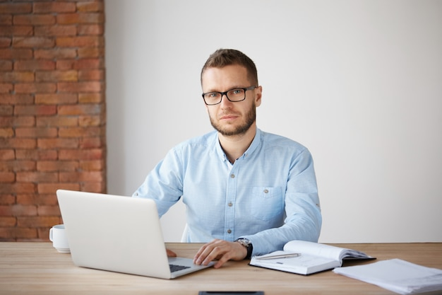 Portret van ernstige volwassen ongeschoren zakenman in glazen en blauw shirt zittend aan tafel, werken op laptopcomputer, taken neerschrijven in notitieblok met ontspannen expressie.