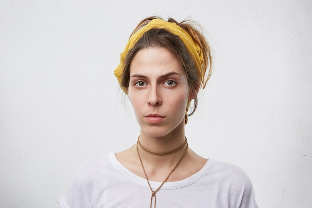 Portret van ernstige vrouw in casual t-shirt serieus kijken.