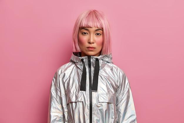 Portret van ernstige vrouw met stijlvol roze kapsel, perfecte frisse schone huid, looks met kalme zelfverzekerde uitdrukking, gekleed in zilveren jasje