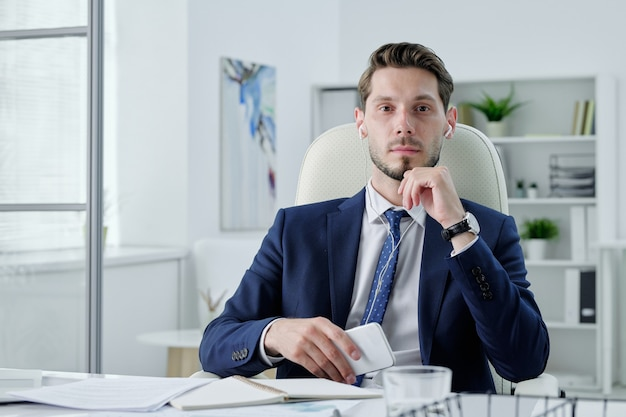 Portret van ernstige zaakvoerder in oortelefoons aan bureau zitten en moderne telefoon in kantoor te houden