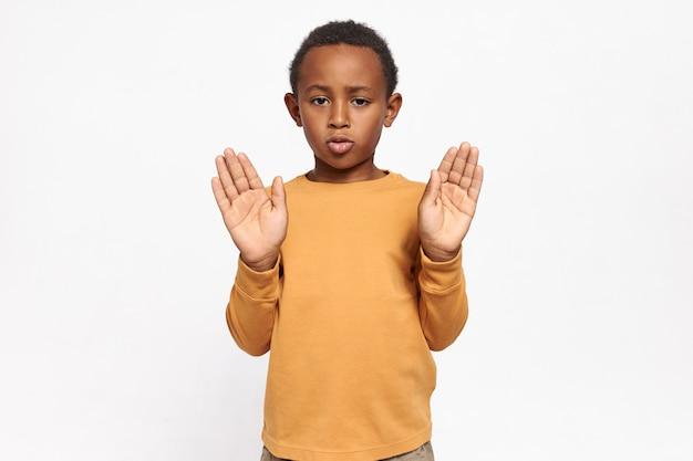 Portret van ernstige zelfverzekerde afro-amerikaanse schooljongen in sweatshirt reiken zijn handen met palmen open stop gebaar maken