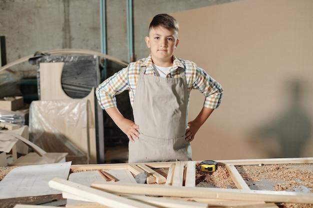 Portret van ernstige zelfverzekerde tiener in schort hand in hand op de heupen aan bureau met houten stukken en krullen in timmerwerkwinkel