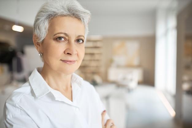 Portret van ernstige zelfverzekerde vrouw van middelbare leeftijd met grijs kort haar, groene ogen, rimpels en charmante glimlach poseren binnenshuis met gevouwen armen