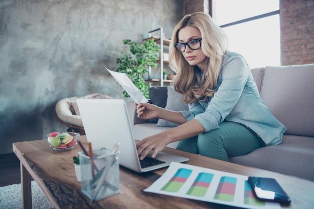 Portret van ervaren bekwame slimme slimme golvende haired dame die op laptop werkt