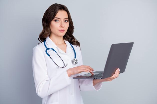 Portret van ervaren infectie specialist meisje laptop gebruikt klaar voor covid19 longontsteking behandeling dragen witte jas geïsoleerd over grijze kleur achtergrond
