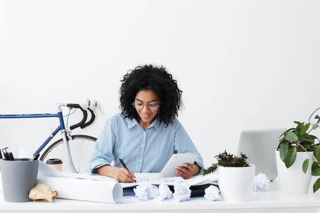 Portret van ervaren professionele jonge donkere vrouwenarchitect die digitale tablet houdt