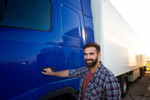 Portret van ervaren vrachtwagenchauffeur die zich door zijn semi vrachtwagen lang voertuig bevindt.