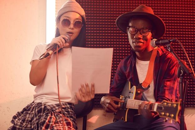 Portret van etnisch muzikaal duo dat gitaar speelt en lyrische liedjes zingt tijdens repetitie