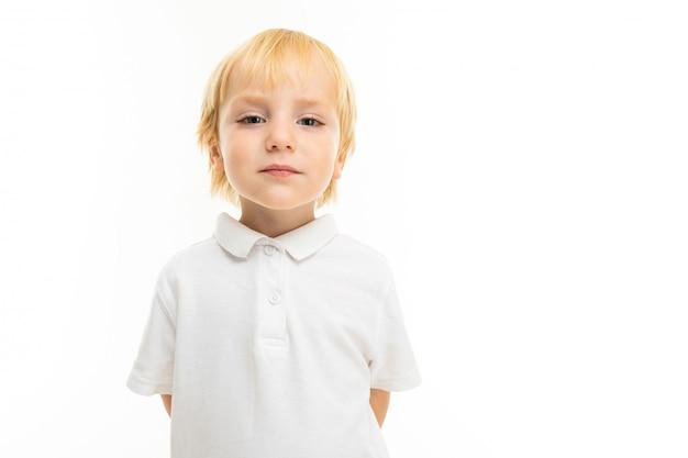 Portret van europese blonde jongen draagt een wit t-shirt op een witte muur