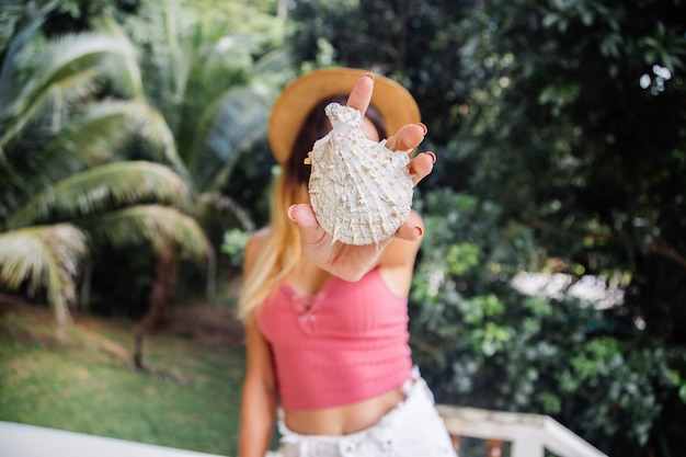 Portret van europese fitte slanke mooie vrouw zonder make-up, natuurlijk licht, met lang haar, roze zomertopje en strohoed