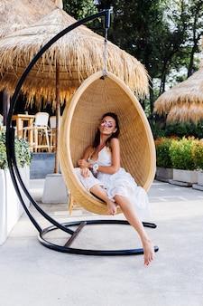 Portret van europese romantische vrouw in witte zomerjurk buiten hoteltoevlucht als stoel van het eierro.