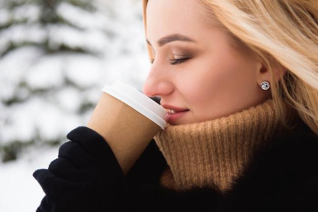 Portret van europese stijl modieuze vrouw koffie drinken in winter park.