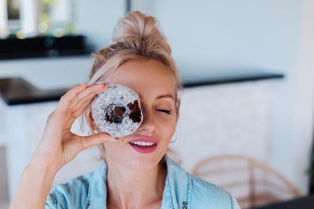 Portret van europese vrouw met blonde haren genieten van donuts in keuken thuis villa.