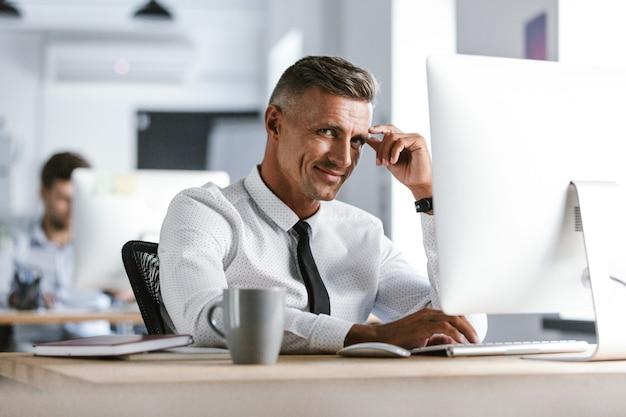 Portret van europese zakenman 30s dragen witte overhemd en stropdas zitten aan de balie in kantoor, en werken op de computer